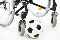 Wheelchair for invalid or disabled person and soccer ball Stock Image