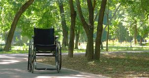 Wheelchair left empty in park stock video footage