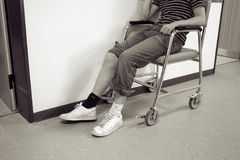 Wheelchair leg accident. Person in wheelchair after having knee injury or accident. Hospital corridor monochrome royalty free stock photography