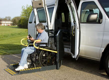 Wheelchair lift van. Disabled man using the remote control on a wheelchair lift van royalty free stock image
