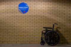 Wheelchair with No Smoking Sign. A wheelchair sits outside a wall where a no smoking sign hangs dilapidated on the wall Stock Photo