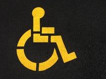 Wheelchair Painted on Asphalt. Yellow handicapped wheelchair symbol painted on black asphalt royalty free stock image