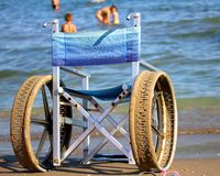 Wheelchair with perforated wheels on the Sea Beach Royalty Free Stock Photo