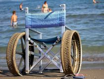 Wheelchair with perforated wheels for swimming in the sea of peo Stock Photo