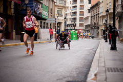 Wheelchair racer. ALBACETE - APRIL 9: Unidentified wheelchair racer and runners on the street during Albacete half marathon on April 9, 2010 in Albacete, Spain Stock Photos
