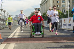Wheelchair racer. Racer in wheelchair crossing the finish line at the Bucharest International Half Marathon on May 18, 2014 in Bucharest, Romania Royalty Free Stock Photography