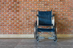 Wheelchair rolls on the sidewalk. Royalty Free Stock Images
