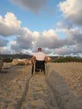 Wheelchair sand. Man in wheelchair advancing through sand Royalty Free Stock Photos