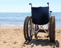 Wheelchair on the sand of the beach Stock Photos