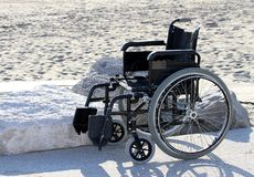 Wheelchair on the sandy beach by the sea in summer Royalty Free Stock Photo
