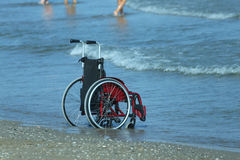 Wheelchair on the shore by the se