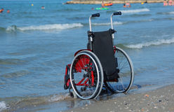 Wheelchair on the shore by the sea on a hot sunny summer day Stock Photos