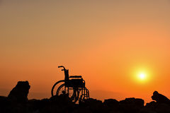 Wheelchair silhouette and sunrise. Disability is the consequence of an impairment that may be physical, cognitive, mental, sensory, emotional, developmental, or Stock Image