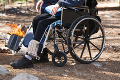 Man in a wheelchair in a park near the fire. Royalty Free Stock Image