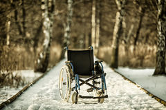 Wheelchair on the snowy road Stock Photography