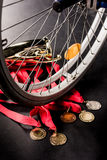Wheelchair standing on gold medals with red ribbons and champion goblet Stock Photos