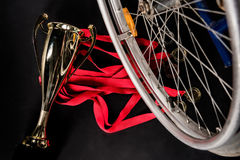Wheelchair standing on gold medals with red ribbons and champion goblet Royalty Free Stock Photography