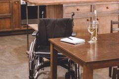Wheelchair standing near table with wine bottle, glasses, notebook. And pen royalty free stock images