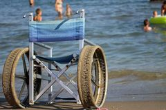 Wheelchair with steel wheels to enter the sea for people with di Royalty Free Stock Photos
