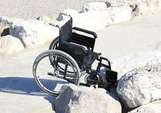 Wheelchair stuck on the rocks by the sea Stock Images