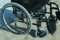 Wheelchair stuck in the sand on the seashore Stock Image