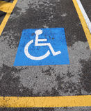 Wheelchair symbol on a car reserved parking Royalty Free Stock Photography
