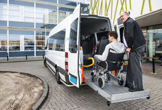 Wheelchair taxi pick up. The driver of a wheel chair taxi, helping a disabled men in a wheel chair, using the lift in the back of his mini van Stock Images