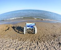 Wheelchair to move around on the beach and the sea Stock Image