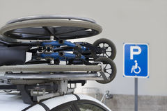 Wheelchair transported on a cars roof. Stock Photography