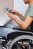 Wheelchair user with calculator Stock Photo