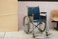 Wheelchair beside the wall Stock Photography