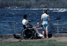 Wheelchair Watching Kayaker. Man in wheelchair and woman watching kayaker on the Ottawa River. Ottawa, Ontario Royalty Free Stock Photos