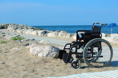 Wheelchair with wheels locked in the sand summer Stock Photo