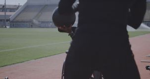 Wheelchaired athlete and trainer throwing medicine ball. Medium shot of a wheelchaired athlete and his trainer working out with a medicine ball stock video footage