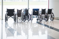 Wheelchairs for elderly and disabled passengers at the airport Stock Photos