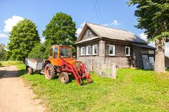 Wheeled agricultural tractor near the wooden house. In the village in summertime Stock Photos