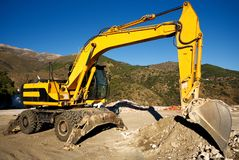 Wheeled excavator, sitting motionless in the Spanish hills. A wheeled excavator, on a break from being used to clear land on the outskirts of the hillside Stock Photography