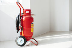 Wheeled fire extinguisher. In a white commercial building Stock Photos