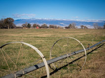 Wheeled irrigation in field in western colorado with farms and s Royalty Free Stock Photo