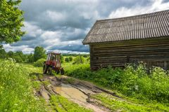 Wheeled tractor on a country road. Royalty Free Stock Photography