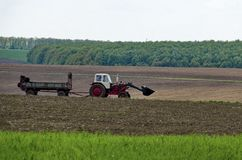 Wheeled tractor distribute manure over a field Stock Photo