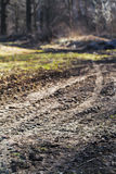 Wheeled tractor tracks in dirt country road Stock Photos