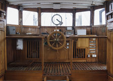 Wheelhouse of and historic ship. Wheelhouse, helm wheel and control panels in an old wooden boat royalty free stock images