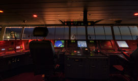 Wheelhouse in modern ship. Bridge with radars, controls, charts, steering panels and command control station. No logos or trademarks on this photo Royalty Free Stock Image