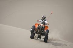 Wheelie adolescente do cavaleiro do quadrilátero nas dunas fotografia de stock royalty free