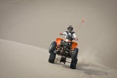 Wheelie adolescente do cavaleiro do quadrilátero nas dunas foto de stock