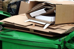 Wheelie bins. Green wheelie bins with cardboard royalty free stock photos