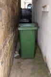 Wheelie bins in a  dingy British alley way. Wheelie bins in a dingy alley way. British domestic household waste storage. Green wheelie bin for garden waste and Royalty Free Stock Photo