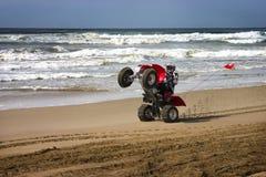 Wheelie del cavaliere di ATV sulla spiaggia Fotografie Stock