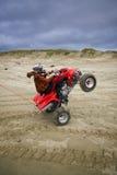 Wheelie del cavaliere di ATV sulla spiaggia Fotografia Stock Libera da Diritti